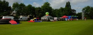 An event complete with various inflatable games, laser tag and rock climbing wall on a grass field
