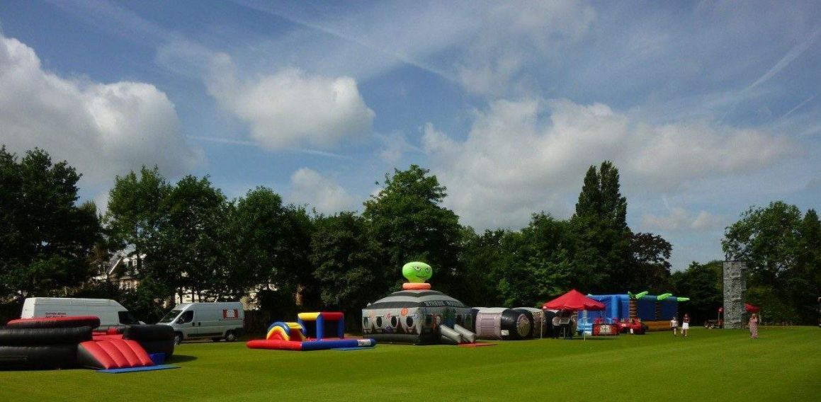 A selection of inflatable activities on a field at a family fun day. Activities include inflatable games, laser tag and rock climbing