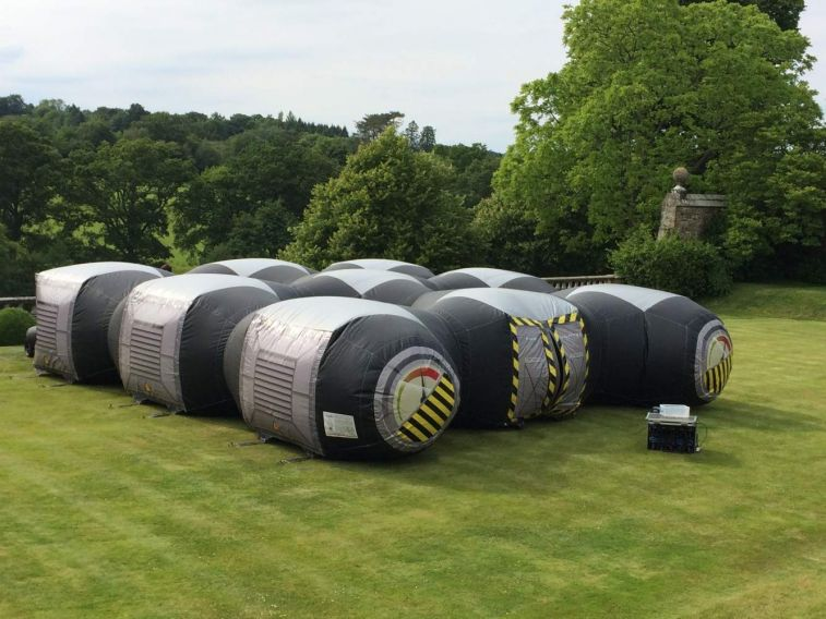 Inflatable laser tag game set up in a garden for a laser tag party. The game is played inside the inflatable arena which is darkened and has lots of hiding places.