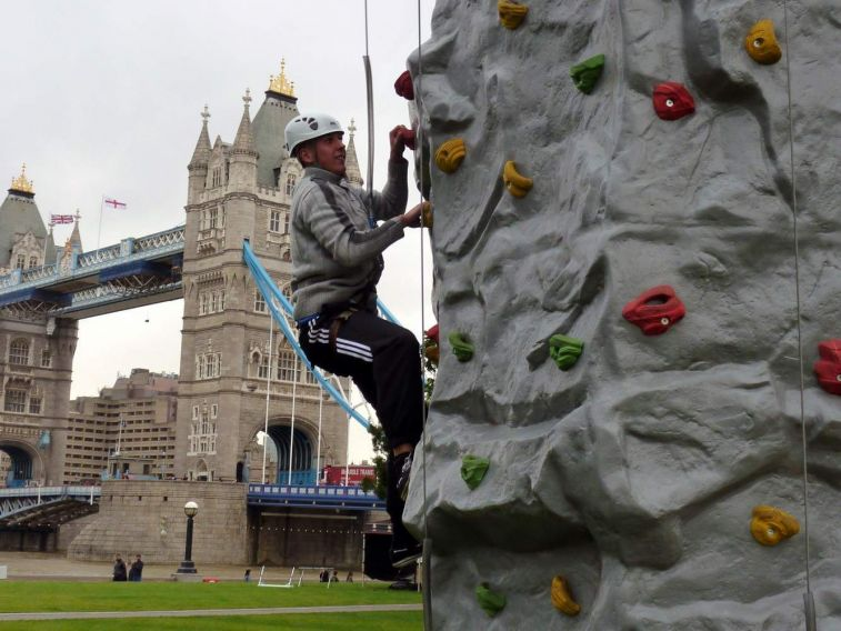 Rock climber ascending the mobile rock climbing wall at an event next to Tower Bridge in Central London. The mobile climbing wall is on the banks of the River Thames with a male climber wearing a harness and rock climbing helmet.