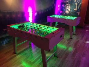 A pair of LED foosball tables with green playing surface selected.
